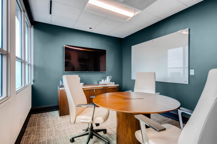 Boulder Office round table with chairs and mounted whiteboard