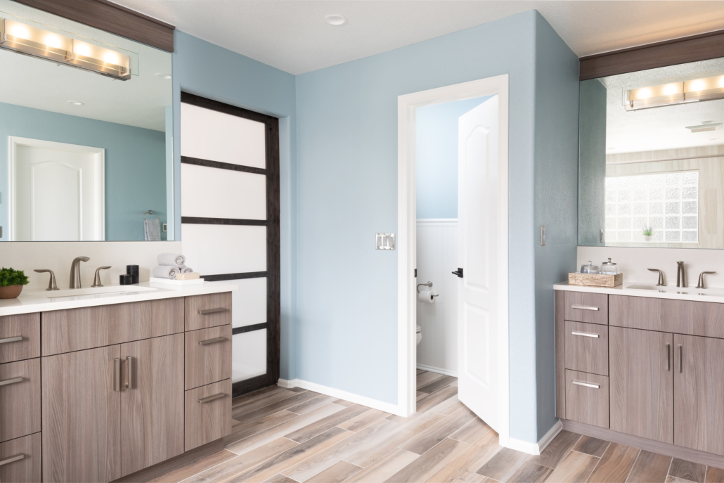 Bathroom with wood cabinets mirrors and unique light fixtures complemented by blue walls
