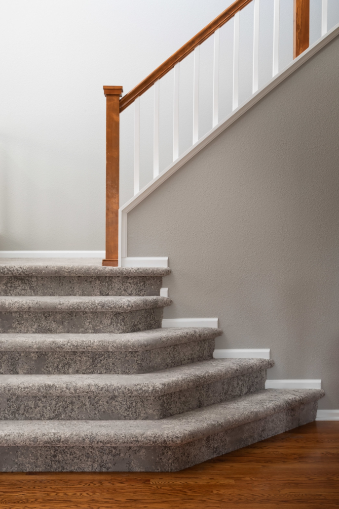 carpet staircase with wood railing