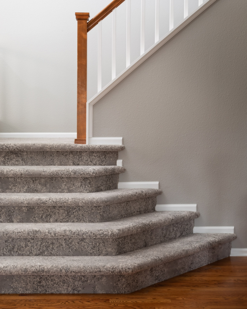 carpet staircase with wood railing close-up