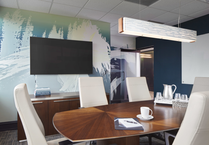 conference room with wood table leather office chairs and abstract wall art