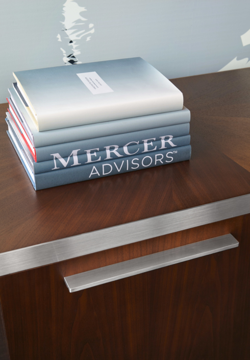 Stack of books with Mercer Advisors Logo displayed across the covers